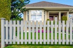 Деревянные загородка и дом в предпосылке Стоковое Изображение