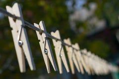 Деревянные зажимки для белья на веревочке веся в перспективе, в осени, стоковые фото