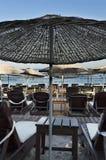 Деревянные зонтики пляжа и loungers солнца с морем на горизонте Стоковые Изображения