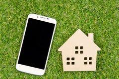 Деревянные игрушка и Smartphone дома на земной зеленой траве с экземпляром Стоковое Изображение RF