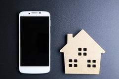 Деревянные игрушка и Smartphone дома на черной предпосылке с sp экземпляра Стоковое Фото