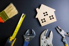 Деревянные инструменты игрушки и конструкции дома на черной предпосылке с Стоковая Фотография
