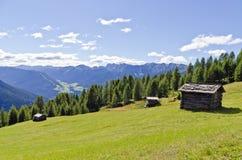 Деревянные кабины горной вершины на луге Стоковые Изображения RF
