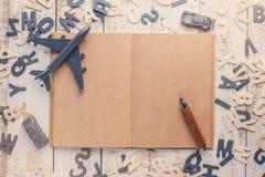 Деревянные карандаш и самолет забавляются на тетради пустой страницы Стоковая Фотография