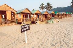 Деревянные коттедж и кабины курорта песчаного пляжа с знаком не нарушают наших гостей Стоковые Фотографии RF