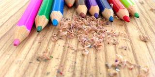 Деревянные красочные карандаши с точить shavings, на деревянном столе Стоковые Изображения RF
