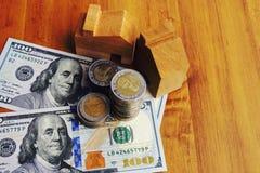 Деревянные кукольный дом и монетки на банкноте доллара США стоковые изображения