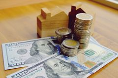 Деревянные кукольный дом и монетки на банкноте доллара США стоковое фото