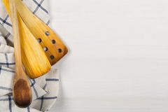 Деревянные ложки с голубым и белым полотенцем кухни на белое деревянном Стоковые Фото