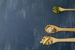 Деревянные ложки с ингредиентами для подготовки мяса с картошками и cilantro стоковые изображения