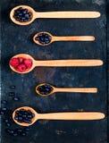 Деревянные ложки с сортированными ягодами на предпосылке старых ржавых металлов, концепции натуральных продуктов, detoxification стоковые изображения rf