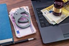 Деревянные молоток, наручники и счеты евро, компьтер-книжка стоковое изображение