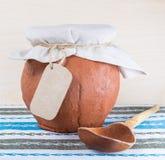 Деревянные ложка и глиняный горшок с тканью Стоковая Фотография