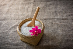 Деревянные ложки и корзина риса жасмина на деревянном Стоковая Фотография