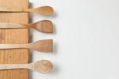 Деревянные ложки на прерывая доске на белой предпосылке Стоковые Фото
