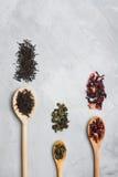 Деревянные ложки с различными листьями чая на сером конкретном backgro Стоковые Изображения