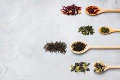 Деревянные ложки с различными листьями чая на сером конкретном backgro Стоковые Изображения RF
