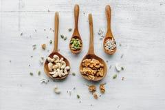 Деревянные ложки с семенами и гайками на белой таблице Стоковые Изображения RF