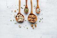 Деревянные ложки с семенами и гайками на белой таблице Стоковая Фотография RF