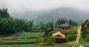 Деревянные дома в деревне с предпосылкой горы Стоковое Изображение RF