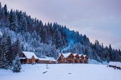 Деревянные дома в лесе зимы снежном Стоковое фото RF