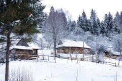 Деревянные дома в лесе покрытом с снегом Стоковая Фотография