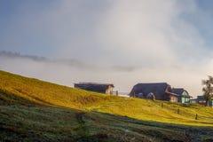 Деревянные дома на холме на предпосылке тумана Стоковое фото RF