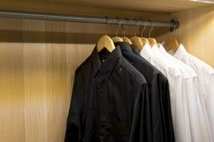 Деревянные одежды кладут на полку с белыми и черными рубашками Стоковое Изображение
