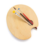 Деревянные палитра и paintbrush на белизне стоковые изображения