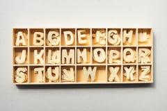 Деревянные письма алфавита в деревянном контейнере на белой предпосылке стоковая фотография rf