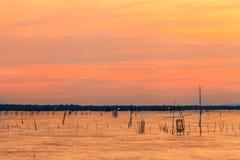 Деревянные пристань или мола остаются на голубом заходе солнца озера и пасмурном sk Стоковые Изображения RF