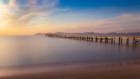 Деревянные пристань/мола, playa de muro, Alcudia, восход солнца, горы, уединенный пляж, золотой солнечный свет, отражение, красив стоковое фото rf