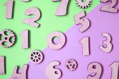 Деревянные пурпурные номера на пастельной покрашенной предпосылке стоковые фотографии rf