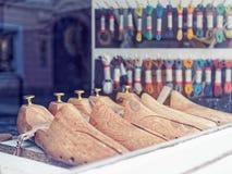 Деревянные пусковые площадки ботинка в окне магазина Изготовление и ремонт обуви Стоковые Фото