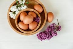 Деревянные плиты с ветвями яичек, белых и фиолетовых сирени деревянное предпосылки белое Взгляд сверху, Croped Стоковые Изображения