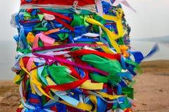 Деревянные ритуальные штендеры с красочными лентами Hadak на ветре на накидке Burkhan озеро baikal olkhon Россия озера острова ba стоковые изображения rf