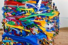 Деревянные ритуальные штендеры с красочными лентами Hadak на ветре на накидке Burkhan озеро baikal olkhon Россия озера острова ba стоковые фото