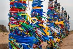 Деревянные ритуальные штендеры с красочными лентами Hadak на ветре на накидке Burkhan озеро baikal olkhon Россия озера острова ba стоковое изображение