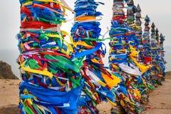 Деревянные ритуальные штендеры с красочными лентами Hadak на ветре на накидке Burkhan озеро baikal olkhon Россия озера острова ba стоковые изображения