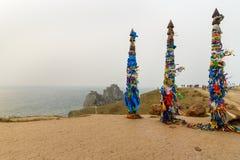 Деревянные ритуальные штендеры с красочными лентами Hadak на накидке Burkhan озеро baikal olkhon Россия озера острова baikal Росс стоковые фотографии rf
