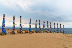 Деревянные ритуальные штендеры с красочными лентами Hadak на накидке Burkhan озеро baikal olkhon Россия озера острова baikal Росс стоковые фото