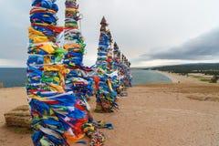 Деревянные ритуальные штендеры с красочными лентами Hadak на накидке Burkhan озеро baikal olkhon Россия озера острова baikal Росс стоковое фото