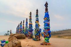 Деревянные ритуальные штендеры с красочными лентами Hadak на накидке Burkhan озеро baikal olkhon Россия озера острова baikal Росс стоковые изображения rf