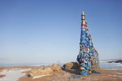 Деревянные ритуальные штендеры с пестроткаными лентами на накидке Burkhan ландшафт острова Olkhon, Lake Baikal стоковые изображения rf