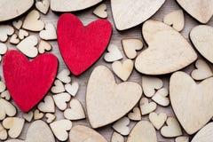 Деревянные сердца, одно красное сердце на предпосылке сердца Стоковые Фото