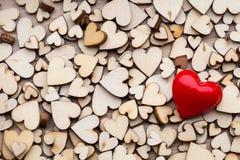 Деревянные сердца, одно красное сердце на предпосылке сердца Стоковое Изображение