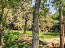 Деревянные скамьи и деревья цветения в городе паркуют Весеннее время в городе Спортивная площадка ` s детей для игр Стоковая Фотография