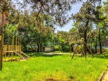 Деревянные скамьи и деревья цветения в городе паркуют около стадиона Весеннее время в городе Спортивная площадка ` s детей для иг Стоковое фото RF