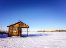 Деревянные спасители дома на береге замороженного озера покрытого с снегом Солнечный выигрыш Стоковое фото RF