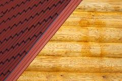 Деревянные стена дома и часть красной крыши от металла кроют крупный план черепицей Стоковое фото RF